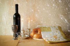 shabbat image. challah bread, shabbat wine and candelas on woode