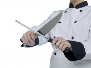 Cropped image of a chef holding knife and grindstone